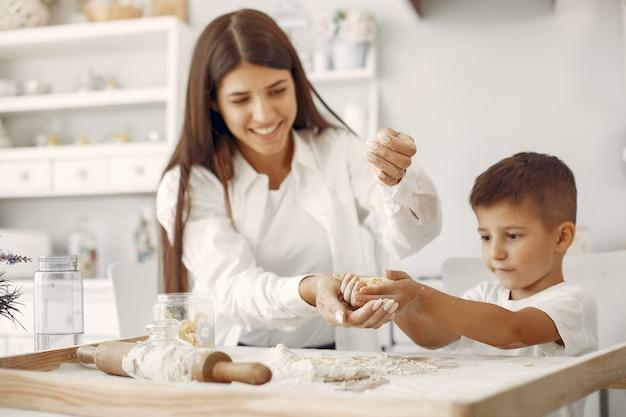Familia sentada en una cocina y cocinar la masa para galletas Foto gratis