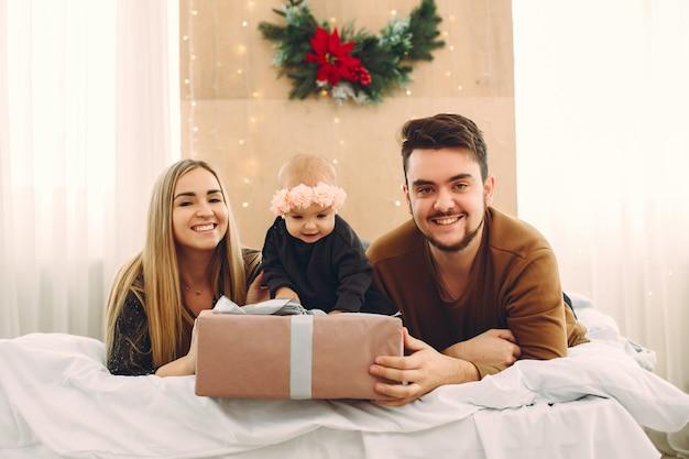 Familia sentada en su casa en una cama con regalos Foto gratis