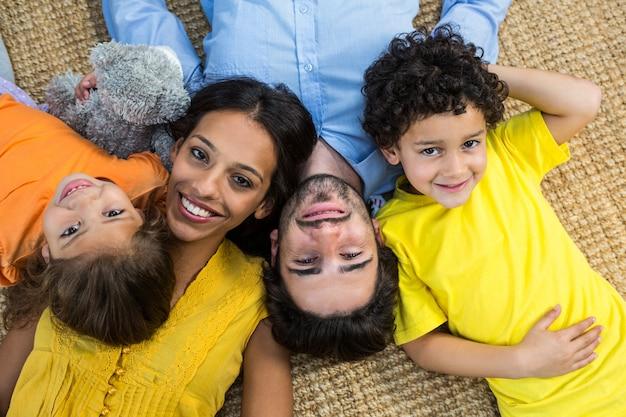Familia sonriente tendido en la alfombra y mirando a la cámara