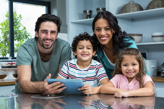 Familia sonriente usando tableta en la cocina Foto Premium