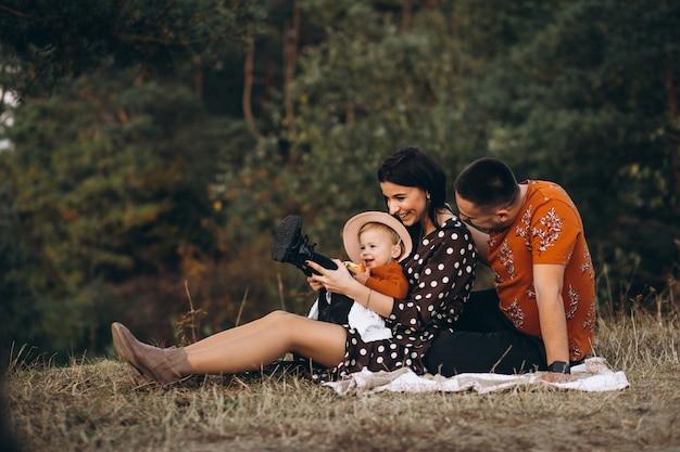 Familia con su pequeña hija haciendo un picnic en un campo Foto gratis