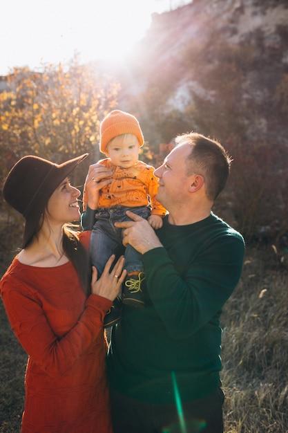 Familia con su pequeño hijo en un parque de otoño Foto gratis