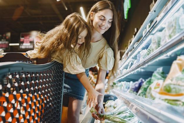 Familia en el supermercado. mujer con camiseta marrón. la gente elige productos. madre con hija. Foto gratis