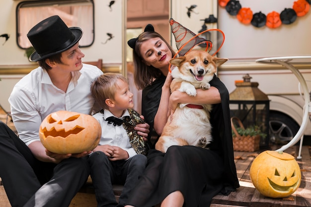Familia de tiro medio con perro con sombrero Foto gratis