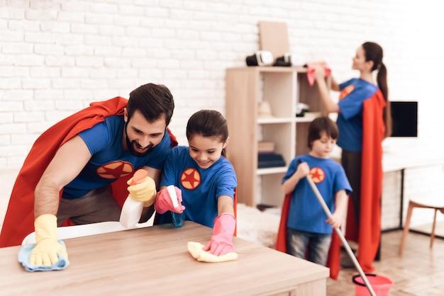Familia en trajes de superhéroes se limpia en casa. Foto Premium