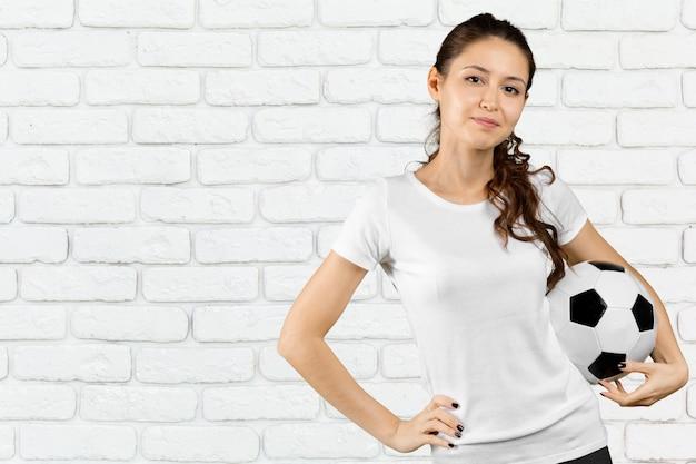 Fan del fubol. mujer hermosa joven que sostiene el balón de fútbol sobre fondo aislado Foto Premium