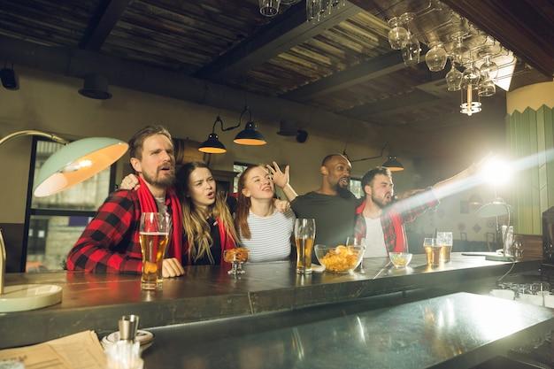 Fanáticos del deporte que animan en el bar, pub y beben cerveza mientras el campeonato, la competencia continúa Foto gratis