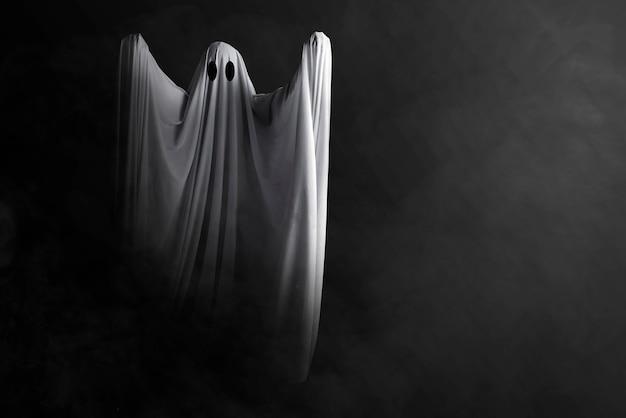 Fantasma blanco inquietante con un fondo oscuro. concepto de halloween Foto Premium
