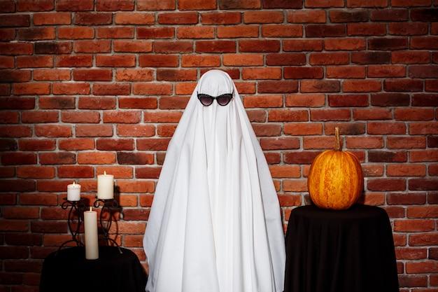 Fantasma en gafas de sol posando sobre pared de ladrillo. fiesta de halloween. Foto gratis