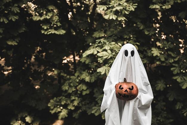Fantasma sosteniendo calabaza y parado en el bosque Foto gratis