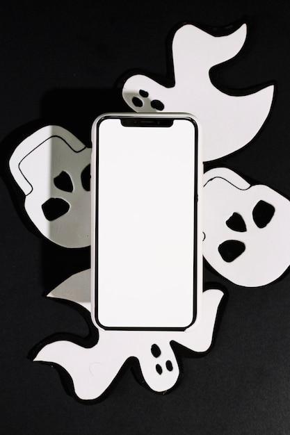 Fantasmas y cráneos hechos a mano con teléfono móvil hechos de papel Foto gratis