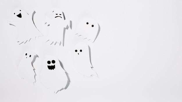 Fantasmas de halloween hechos de papel con caras divertidas Foto gratis