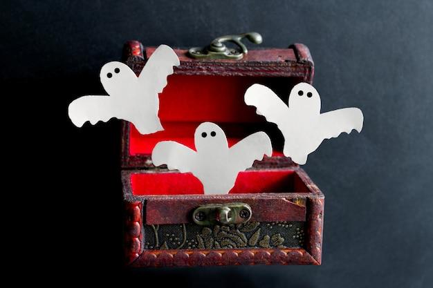 Fantasmas terroríficos cortados en papel salen de un viejo cofre de madera vintage Foto Premium