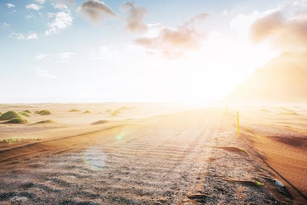Fantástica puesta de sol de las montañas y dunas de arena de lava volcánica a la playa en stokksness. un día caluroso y un desierto Foto Premium