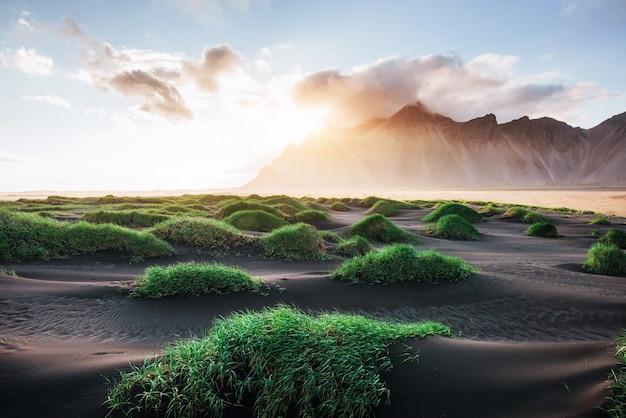 Fantástico al oeste de las montañas y las dunas de arena de lava volcánica en la playa stokksness, islandia. colorido mañana de verano islandia, europa Foto Premium