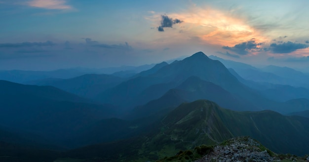 Fantástico amanecer o atardecer sobre la cresta verde de la montaña cubierta de densa niebla azul. sol anaranjado brillante que levanta en cielo nublado suave sobre horizonte distante. belleza de la naturaleza, el turismo y el concepto de viaje. Foto Premium