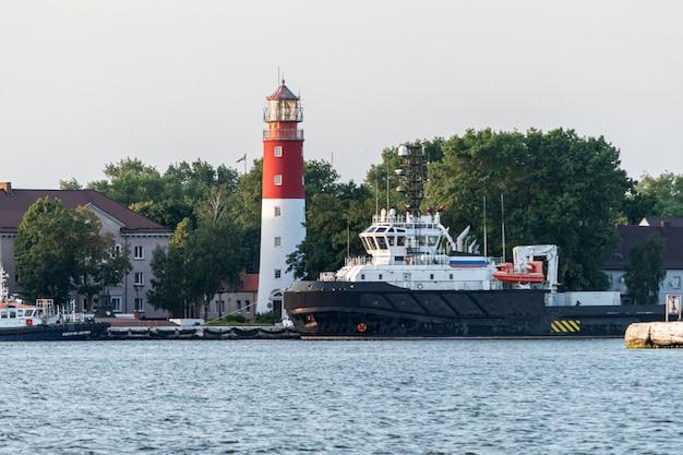 Faro en el puerto. baltiysk ruso hermoso faro. limpiar el cielo azul. Foto Premium