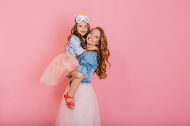 Fascinante madre rizada y hermosa hija de moda en el mismo atuendo posando juntas después de la fiesta de cumpleaños. retrato de niña linda en falda exuberante abraza a su hermana mayor con amor y sonrisa Foto gratis