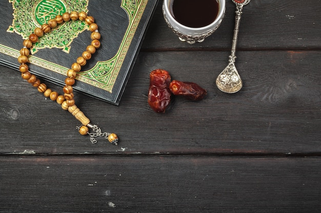 Fecha de frutas, corán y rosarios de madera en el ramadán musulmán de madera, mensaje bendito del viernes y tres meses Foto Premium