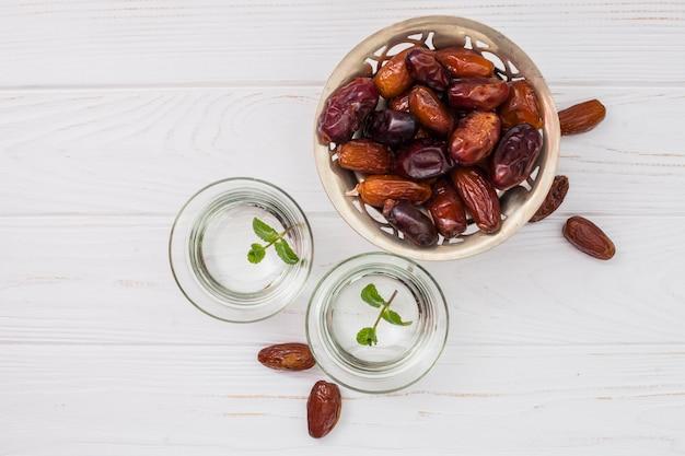 Fechas de fruta en plato pequeño con agua en tazones. Foto gratis