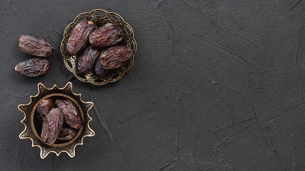 Fechas de fruta seca y dulce en el elegante recipiente de metal de cobre sobre la superficie negra Foto gratis