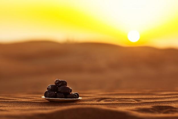 Fechas en un hermoso plato en el desierto en una hermosa puesta de sol, que simboliza el ramadán Foto Premium