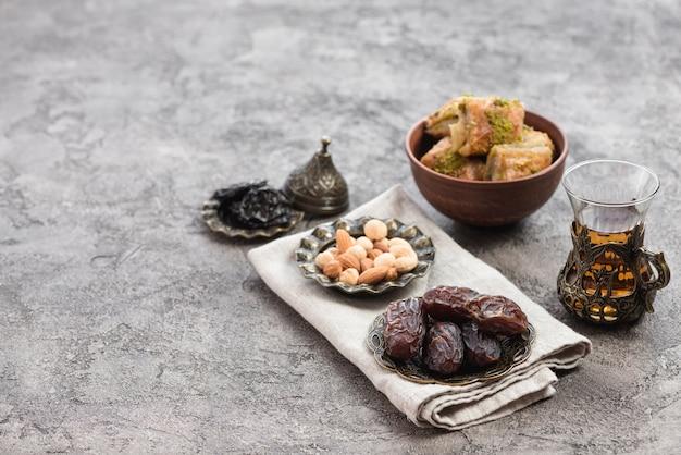 Fechas jugosas; nueces; té de hierbas y dulces de baklava en un tazón sobre un fondo con textura de hormigón Foto gratis