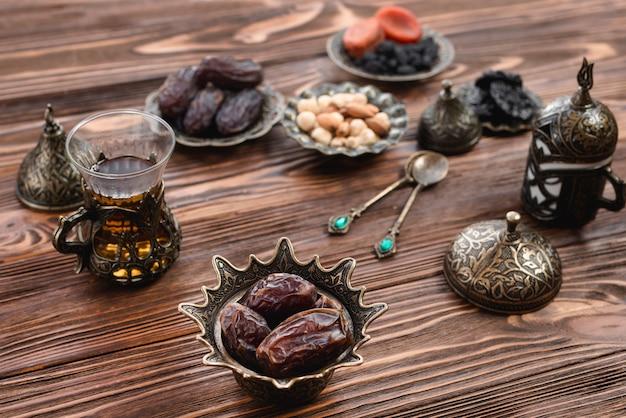 Fechas jugosas en un tazón de hierro árabe con vaso de té en el escritorio de madera Foto gratis