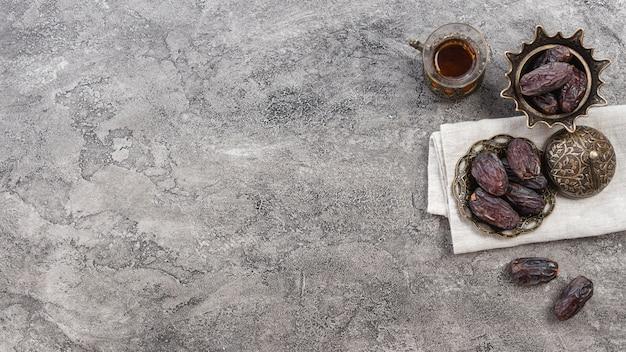 Fechas maduras jugosas y vaso de té sobre fondo de hormigón Foto gratis