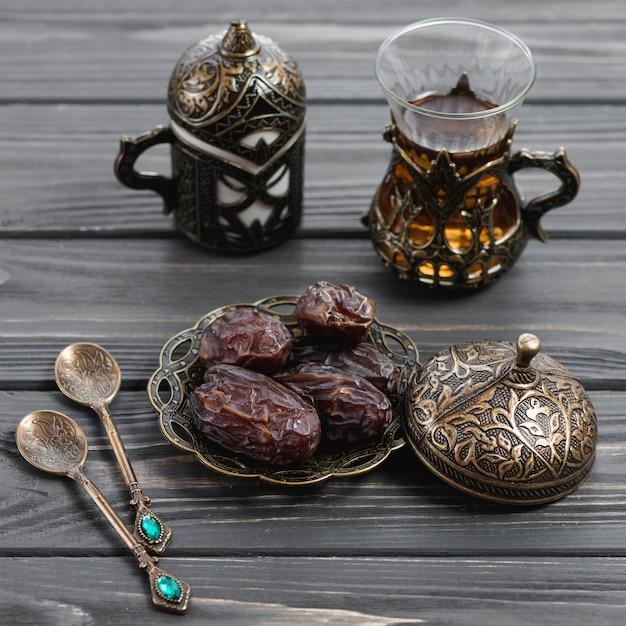 Fechas orgánicas en placa de trabajo de metal artística grabada toreutic y vaso de té en mesa de madera Foto gratis