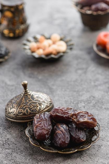 Fechas de palma fresca en la placa de bronce con tapa en la placa de hormigón Foto gratis