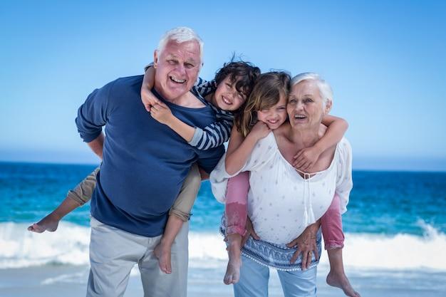 Felices abuelos dando piggy back a los niños Foto Premium
