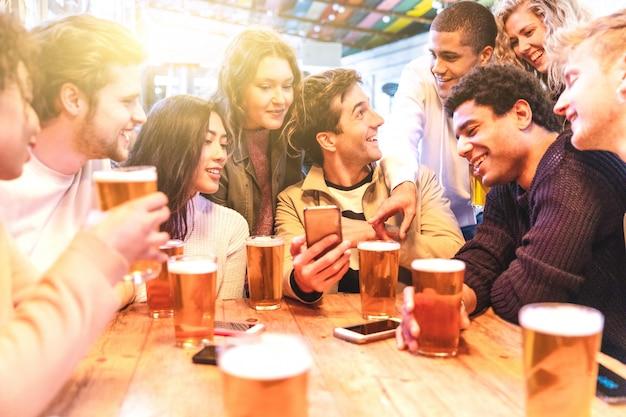 Felices amigos del milenio en un pub bebiendo cerveza Foto Premium