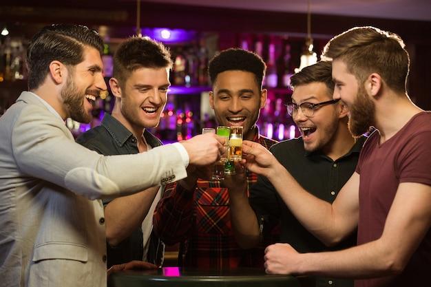 Felices amigos varones bebiendo cerveza y tintineo de vasos Foto gratis
