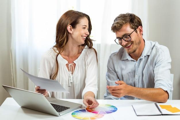 Felices colegas masculinos y femeninos discutiendo muestras de color en la oficina creativa Foto Premium