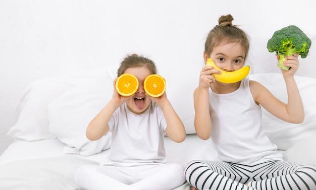 Felices dos lindos niños jugando con frutas y verduras. Foto gratis