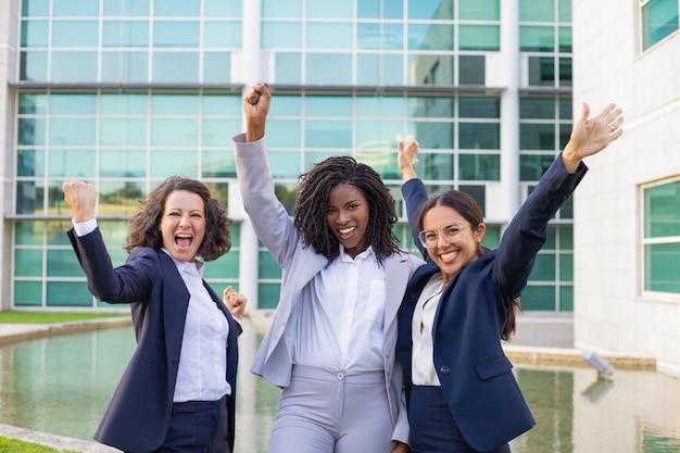 Felices empresarias emocionadas regocijándose por el éxito corporativo Foto gratis