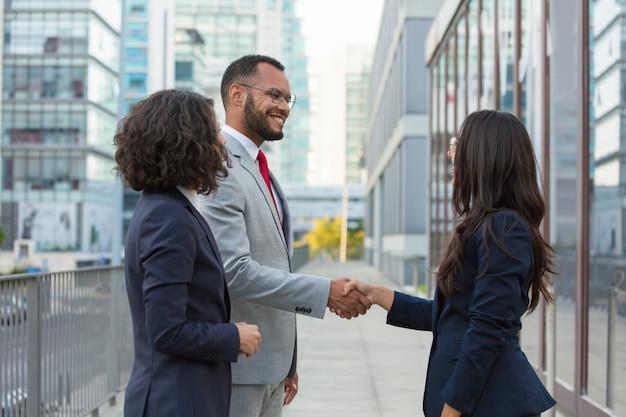 Felices empresarios positivos reunidos afuera Foto gratis