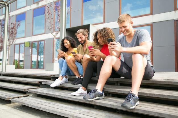 Felices estudiantes multiétnicos sentados juntos Foto gratis