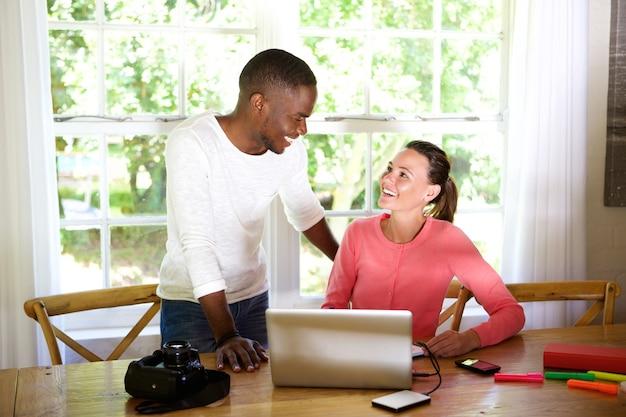 Felices jóvenes amigos con laptop y cámara de fotos en la mesa Foto Premium