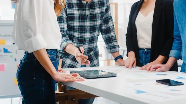 Felices jóvenes empresarios de asia y mujeres de negocios que se reúnen para intercambiar ideas sobre nuevos colegas del proyecto de papeleo que trabajan juntos en la planificación de la estrategia de éxito disfrutan del trabajo en equipo en la pequeña oficina moderna. Foto gratis