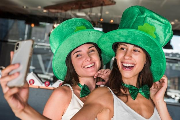 Felices mujeres jóvenes en sombreros de san patricio que toman selfie en teléfono inteligente Foto gratis
