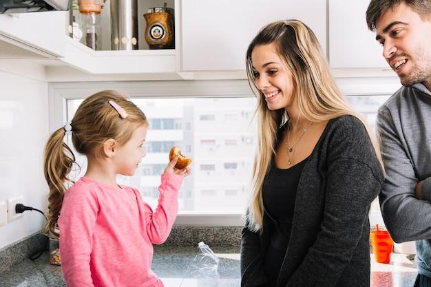 Felices padres mirando a su hija sosteniendo magdalena en la cocina Foto gratis