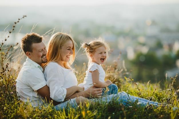 Los felices padres y su pequeña niña descansan en el césped en un hermoso día de verano Foto gratis
