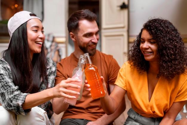 Felices tres amigos brindando por sus bebidas Foto gratis