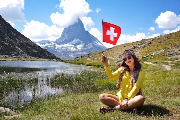 Felicidad mujer asiática sentada y sonriente sosteniendo una bandera suiza cerca del lago alpino de riffelhorn Foto Premium