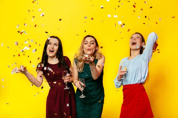 Feliz 8 de marzo. hermosas chicas alegres jugando con confeti, soplando, divirtiéndose juntas Foto gratis