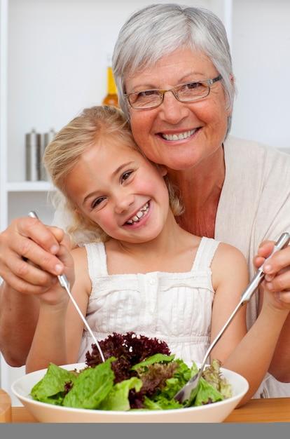 Feliz abuela comiendo una ensalada con nieta   Descargar Fotos premium