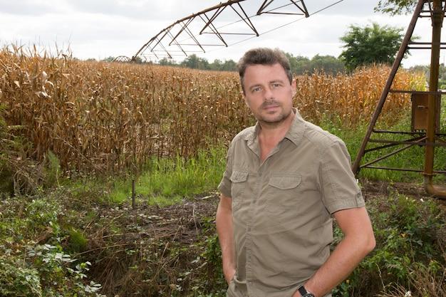 Feliz agricultor en el campo de control de plantas de maíz durante un soleado su Foto Premium