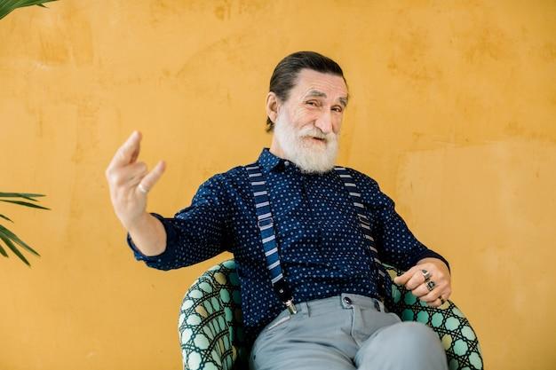Feliz anciano con barba gris, vistiendo ropa elegante de moda hipster, posando en el estudio, sentado frente a la pared amarilla y mostrando rock and roll Foto Premium